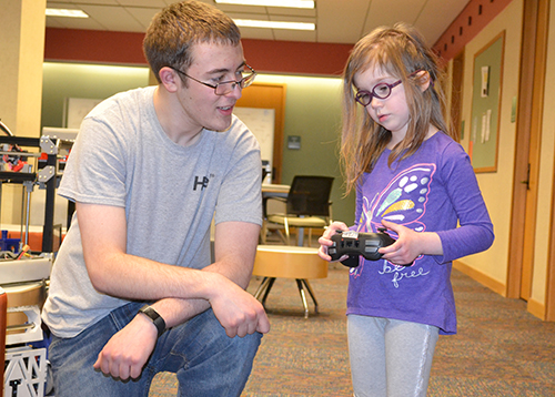 An iRobotics member teaching a local youngster how to operate the robot.