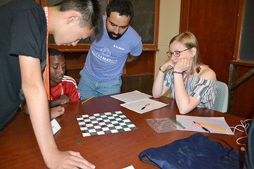 On the final day of camp, campers were allowed to pick whichever games they wanted to play on various sufaces. Here, they're playing  checkers on a