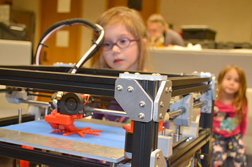 A young participant watches as a 3D printer manufactures a starfish.