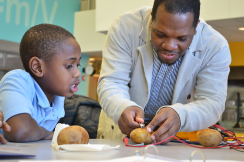 Jerrod Henderson helps a youngster with his potato battery.