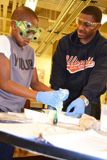 A participant at the Saturday lab session makes slime, assisted by one of the program's mentors.