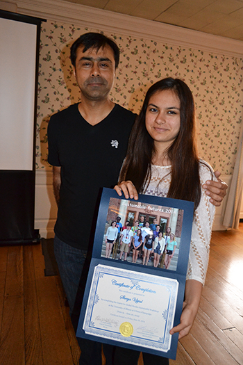 A high school student (right) poses with and her father at the Sustainable Futures Final Presentation event.