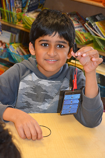 A Dr. Howard School student showing the solar cell he will use to power his solar car.