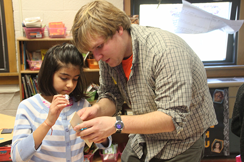 Peter Sokalski (right) helping a fourth grader build her solar car. (Image courtesy of Joe Muskin.)