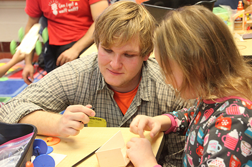 Peter Sokalski (left) helping a fourth grader build her solar car. (Image courtesy of Joe Muskin.)