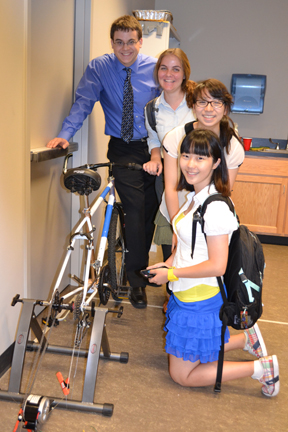 PowerHouse Team poses by their stationary electric bike prototype.