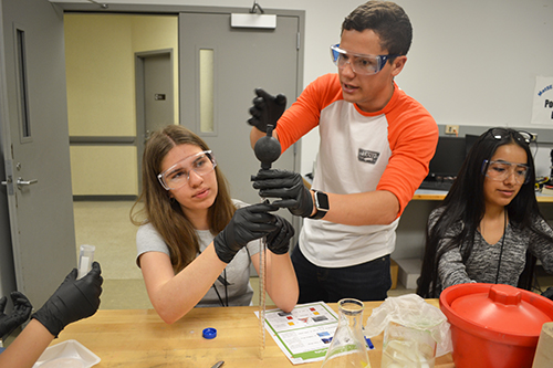 A lab assistant teaches a GLAM camper how to use a piece of equipment during the biomaterials session.
