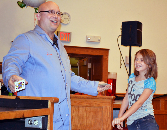 Jesse Miller performs a card trick with the help of a young volunteer.