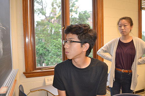 Caption: Weihang Wang (right) watches a Uni student solving a problem.