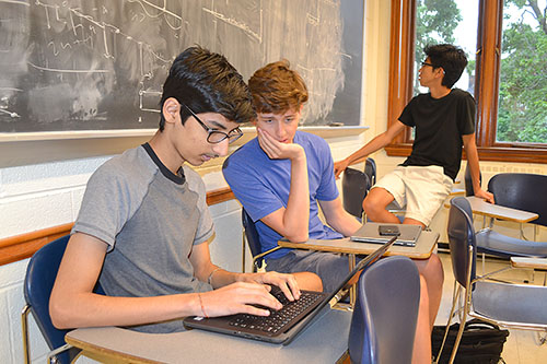 Uni High students Sparsh Singh, Grant Hoey, and Matthew Tang at work doing combinatorics research.