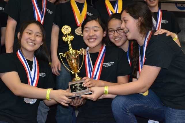 Several Marie Murphy students celebrate over their trophy.