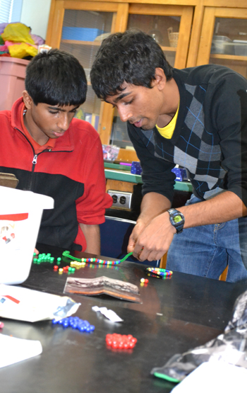 BioE student Manu Kumar (right) works with student during hands-on activity about plasmids.