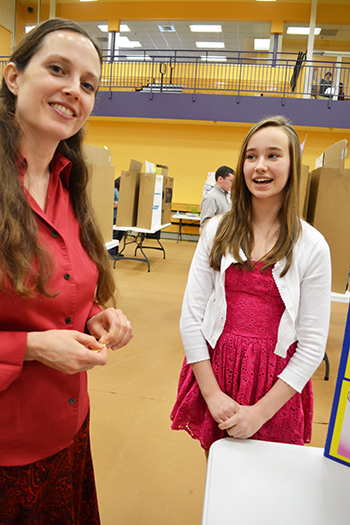 Carrie Kouadio (left) interacts with a student at a local science fair Kouadio helps organize.