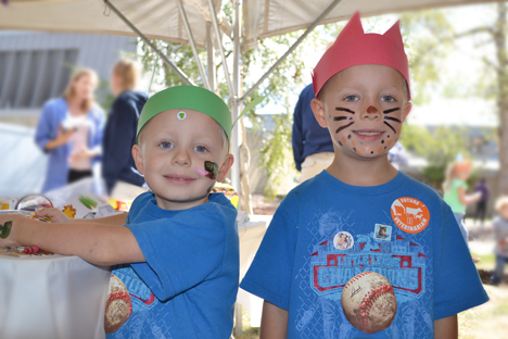 Two local boys display the headbands, facepaint, and tatoos they got at the Kids' Tent.