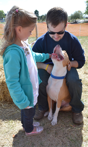 Vet Med student Josh Good and pit bull Kevin have a moment with a young visitor to the Open House.