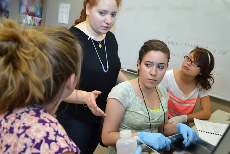 G.A.M.E.S. Bioengineering camp instructor Olivia Cangellaris works with the campers during a hands-on activity with frogs.