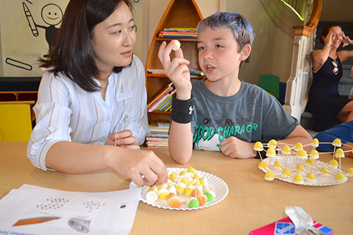 Lili Cai discusses with a child how to arrange the gum drops to form the shape of a molecule.