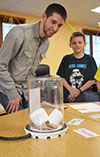 Tyler Haddock (left) and a STEAM Studio student watch as two marshmallows expand as a vacuum is created in the bell jar.