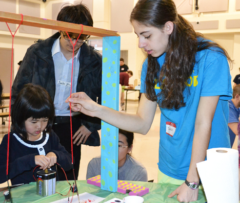 Sarah Stranieri (right) helps 5-year old Kegion do an activity that allows the students to paint using electrical impulses from batteries.