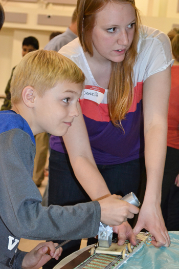Danielle Malone (right) guides 9-year-old Kevin through how to use the catapult.