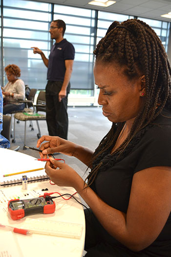 Lillian Perteete, Chicago Vocational Career Academy's instructional technology teacher, prepares to test her circuit.