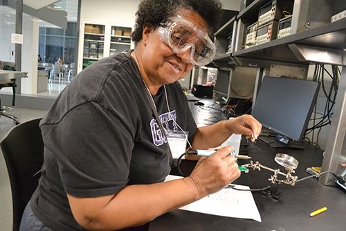 Chicago Vocational Career Academy English teacher Zenobia Jefferson enjoying the soldering hands-on activity.