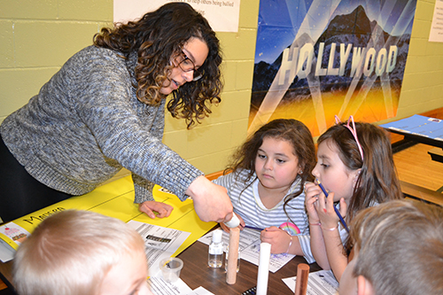 Lina Florez works with young children during Cena y Ciencias.