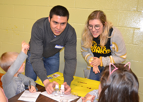 Two Illinois students do an activity with young visitors during Cena y Ciencias