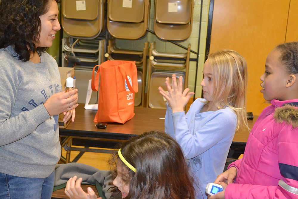 An Illinois student interacts with young visitors during Cena y Ciencias.