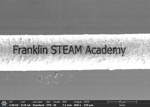 A piece of hair etched with the Franklin logo using a focused ion beam. Dr. Honghui Zhou, an MRL staff scientist who runs this instrument, helped the middle school students etch this and then image it.