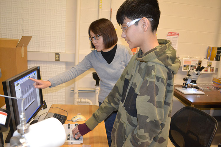 MRL's Jade Wang instructs a Franklin seventh grader about how to use MRL's Scanning Electron Microscope (SEM) during their visit to MRL