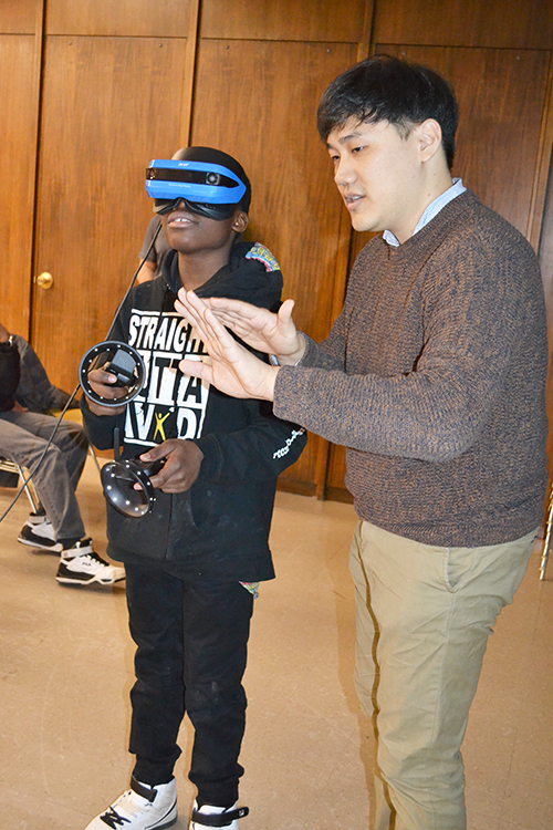 Kisung Kang interacts with a Franklin STEAM Studio student who's experienceing  Virtual Reality during one of the school's field trips to MRL.