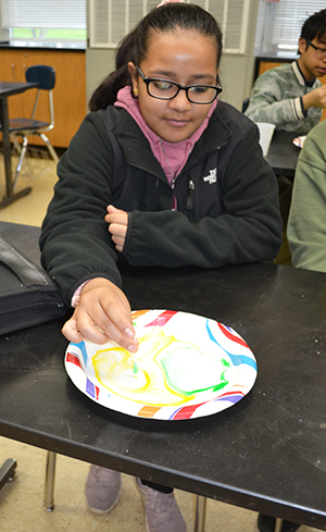 A local eighth grader learns about milk's hydrophobic and hydrophyllic properties.