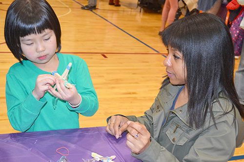 Lonna Edwards (right) helps a student build a catapult.