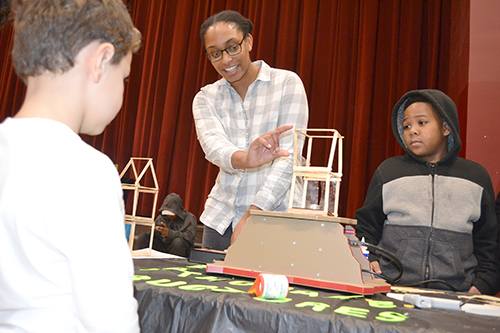 Jamie Clark, a member of the  GEDI organization, tests the  earthquade structure a young visitor built.