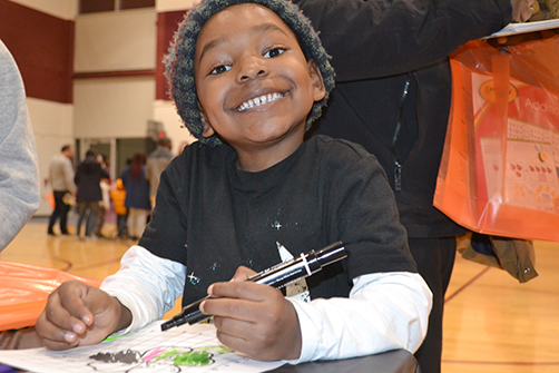 A STEAM night visitor is all smiles while working at the Anamorphic Art Station.