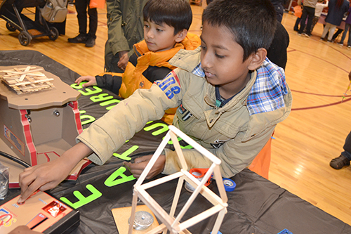 A STEAM night visitor ratchets up the shaking while testing the earthquade structure he built.