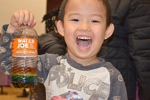 A youngster gleefully shows off the Rainbow Jar he made.