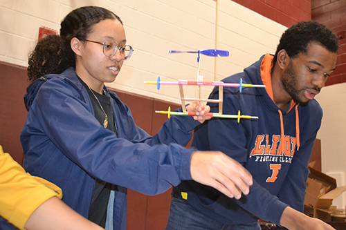 Ashley Mitchell (left) helps a youngster with their rubberband helicopter.