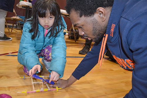Kingsley Okeke (right), helps a young visitor test her rubberband helicopter.