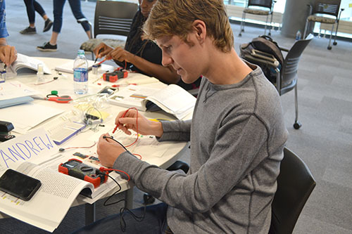 Andrew Wolmer, a Mahomet-Seymour alum and current Illinois secondary science teacher candidate, tests the voltage of the circuit he built.