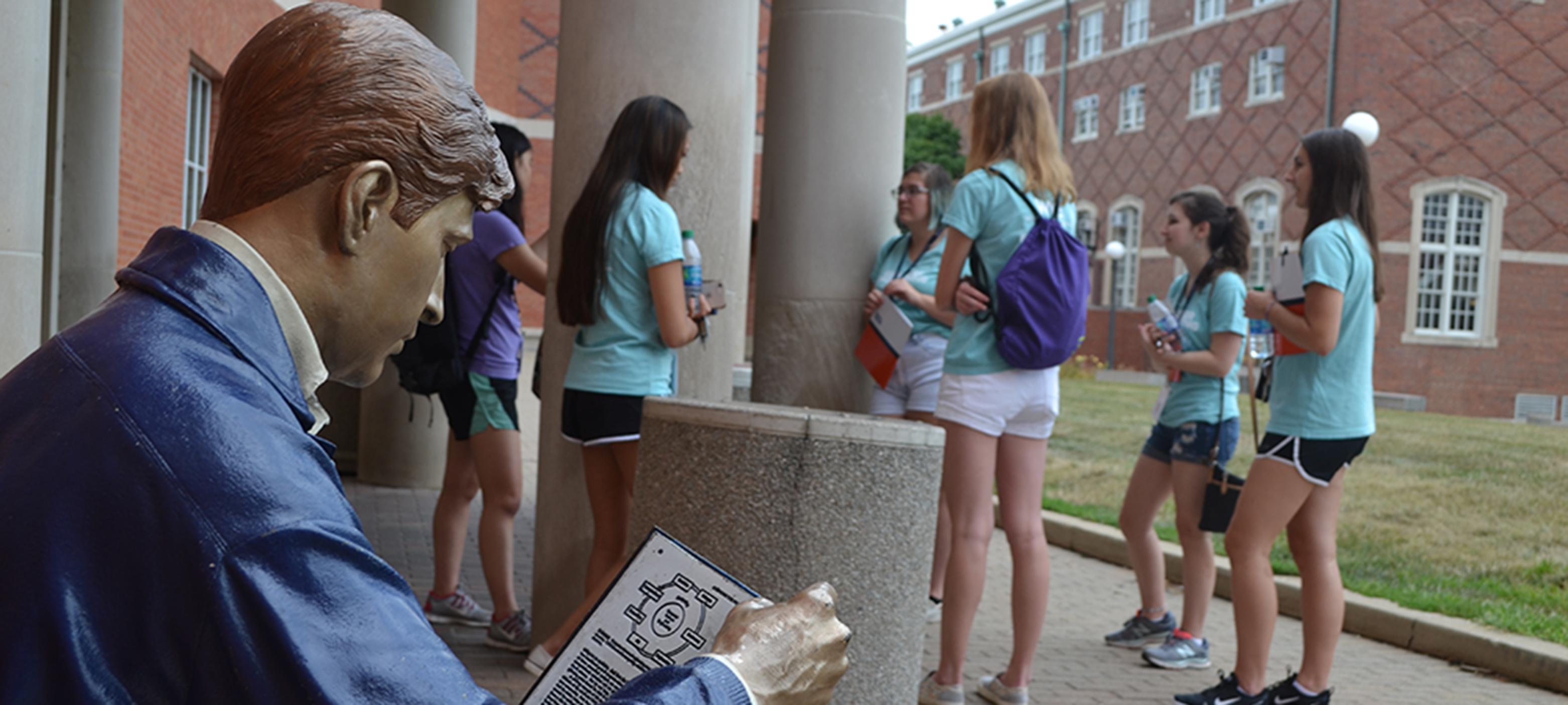 At the fall 2019 WIE Orientation, a group of female engineering freshmen chat on the south portico of Grainger Library as Grainger Bob looks on.