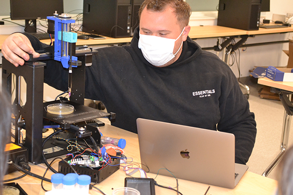 Joshua Whitely makes an adjustment to the 3D Bioprinter during the demo