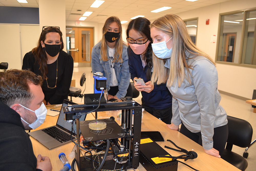 Holly Golecki (second from the left) and the 3D Bioprinter team (left to right) Joshua Whitely, Lauren Ladehoff, Joy Chen, and Lauren Passwater, watch their printer during an imprompteau demo Golecki set up in one of BioE 435's labs.