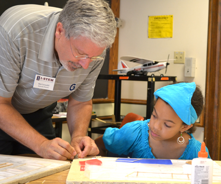 Bob Coverdill helps a camper with her model airplane.