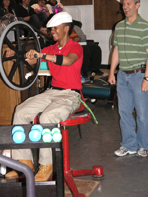 Student helps Professor Pitts demonstrate the conservation of angular momentum.