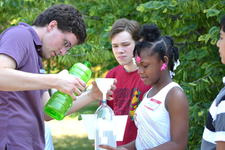 Drew Coverdill (left) and campers filling bottle rocket prior to launch.