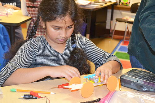 A Dr. Howard school student works on building her solar car.
