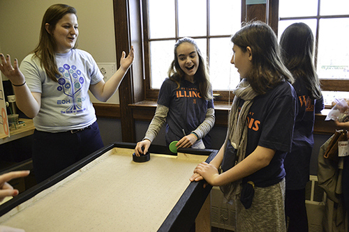 Abby Pakeltis interacting with EOH visitors playing at the air hockey table she helped build.