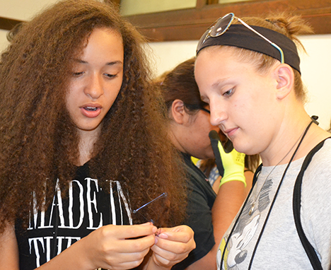 G.A.M.E.S. counselor Grace Pekeltis (right), a sophomore in Materials Science Engineering, and a GLAM camper examine the camper's  memory metal.